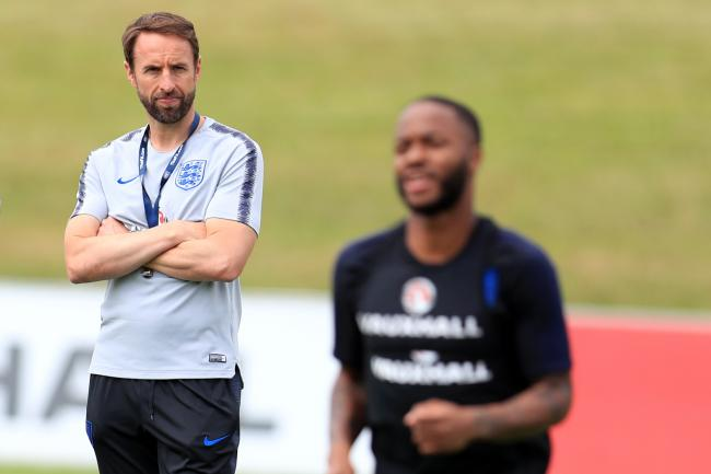 England manager Gareth Southgate watches Raheem Sterling during training