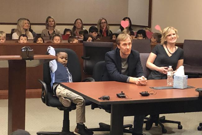 Michael with his class behind him at an adoption hearing