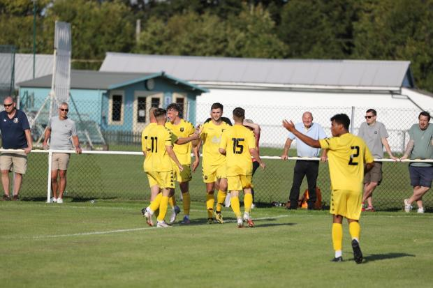 Tadley players rush to celebrate with Andrew Charsley (centre) after his winning goal against Fawley sent them through to the first qualifying round of the FA Cup for the first time. Credit: Elisha Bootham Photography.