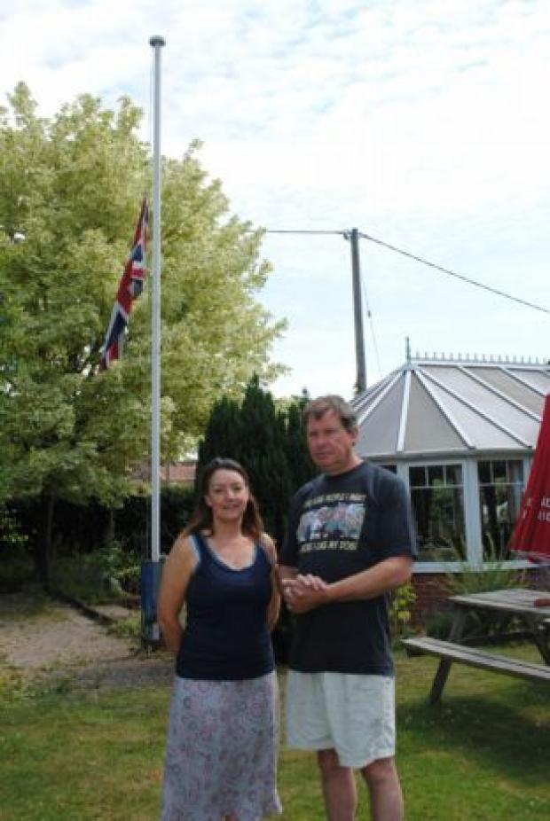 Landlord and landlady Simon and Sharon Bumpstead with their flag at half-mast
