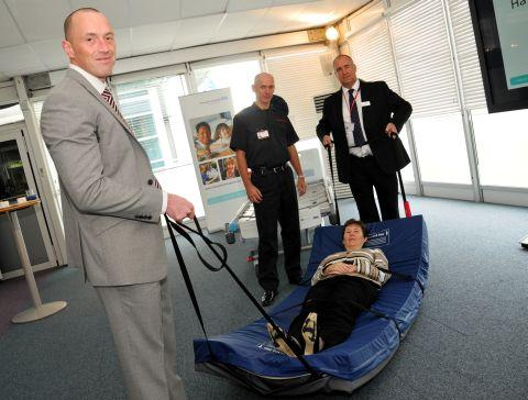 Donna Green chief operating officer, NHS Foundation Trust, tries out the new mattress with (L-R): Graham Ewart of Direct Healthcare Services, Dave Norgate Fire Service group manager for Basingstoke, and Steven Tremarco, Hampshire Hospitals Fire Officer