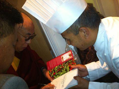 Chef Pemba Lama presents a copy of his cookery book to the Dalai Lama