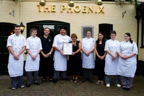 Landlady Sisi Ryder and her husband Andrew (centre) with staff at The Phoenix Inn