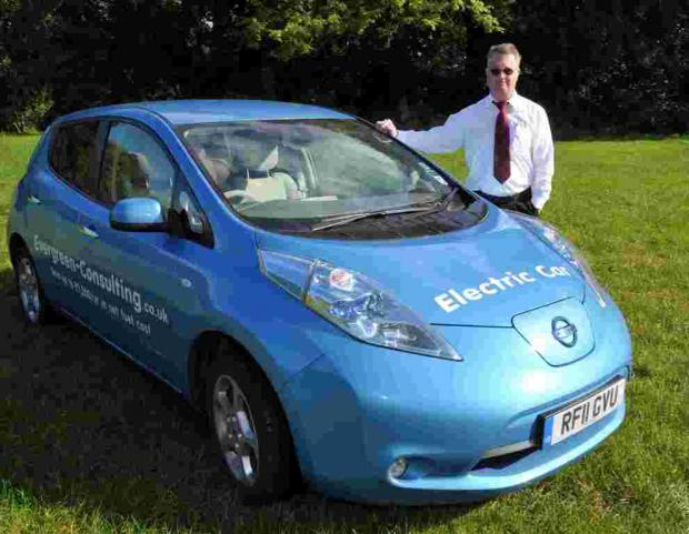 Robert Sharpe of Evergreen Consulting besides his Nissan Leaf electric car