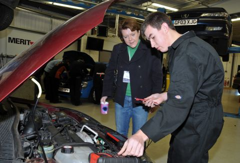 Full-time Level III Automotive student Adam Hayes shows Maria Miller how diagnostic equipment is used on a car