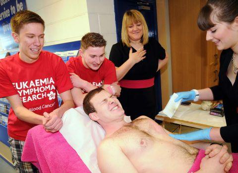Tom Batten having his chest waxed