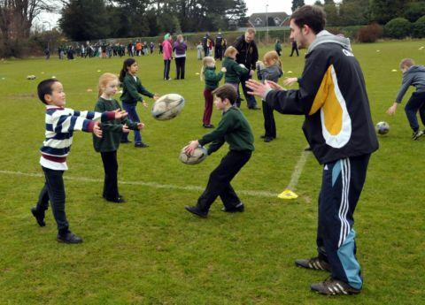 Coaches from Chineham teach pupils from Fairfields Primary School some rugby skills.