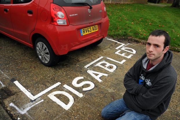 Stephen McGowan next to the disabled bay which was painted around his parked car