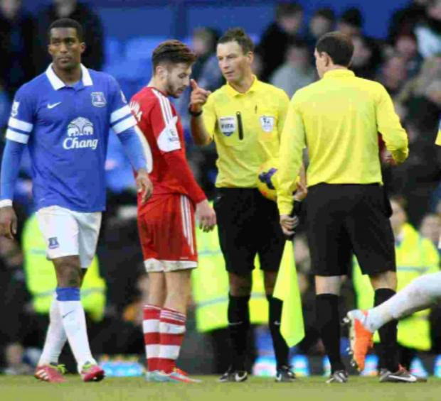 Basingstoke Gazette: Mark Clattenburg has words with Adam Lallana at the final whistle of the Everton v Saints match.