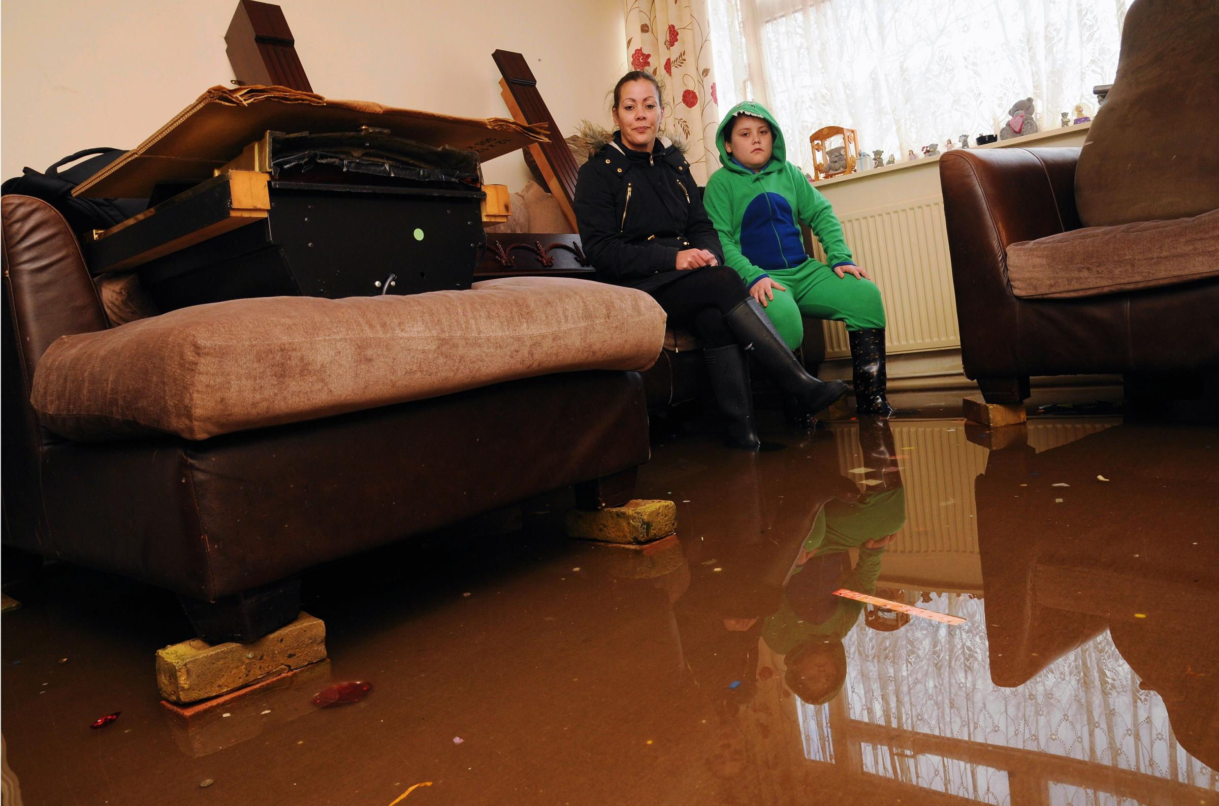 Lola Clayton and her son Kieran Hodge in their flooded home