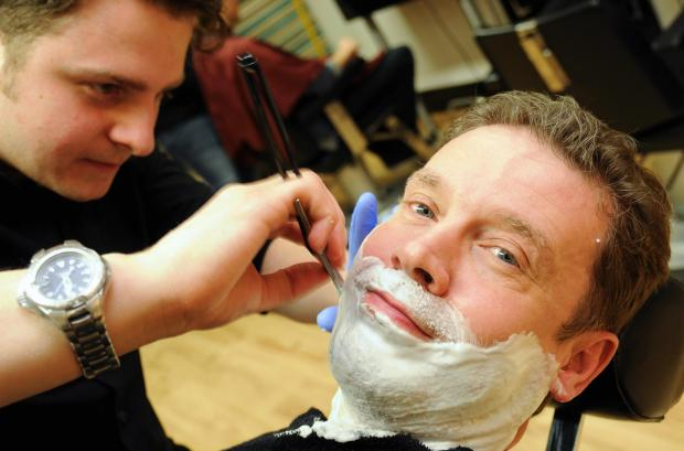 Basingstoke Gazette: Business editor Richard Garfield enjoys a cut-throat shave from Luke Ruffell, of Taylor Made Men's Grooming