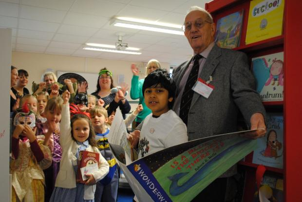 School governor Dave Spencer with pupil Mutahhar Amin, six, and fellow students in the new library