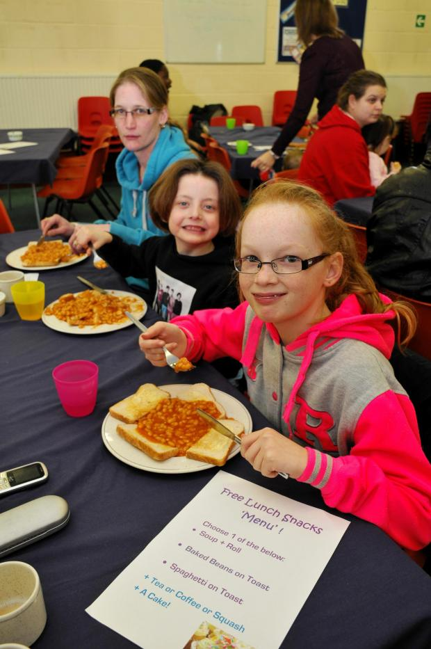 Basingstoke Gazette: Karen Jones and her daughters Daisymae and Emily tuck into free beans on toast at Buckskin Evangelical Church after being evacuated from their home.