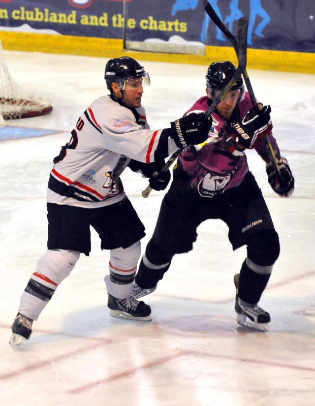 Basingstoke Gazette: Basingstoke Bison player/coach Doug Sheppard battles with a Manchester Phoenix player in a game earlier this season.