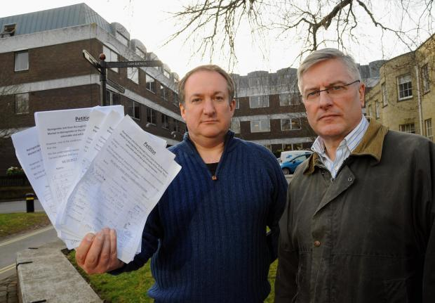 Basingstoke Gazette: Alan Stone and Robert Blay hand in a petition on behalf of the stallholders