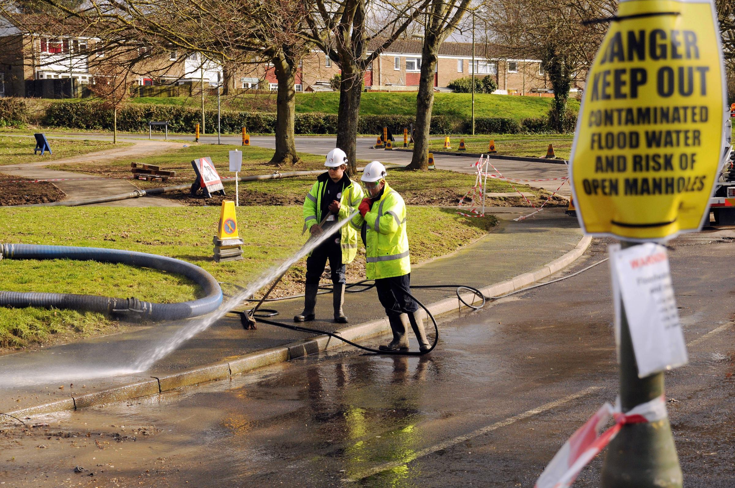 Thames Water workers start the clean-up in Buckskin as the flood waters finally recede.