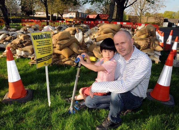 Paul Bensilum and his son Peter near the pile of contaminated sandbags