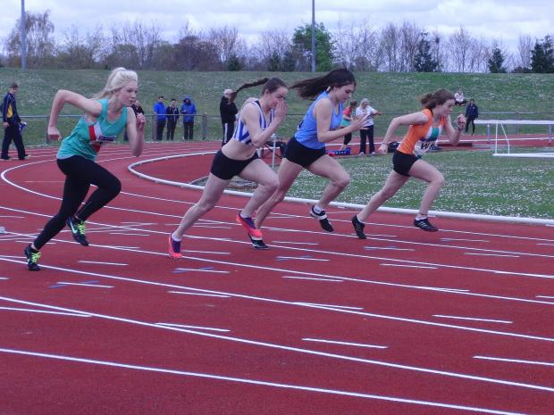 Annie Brookes, in the striped top on her way to a new best at Charlton track
