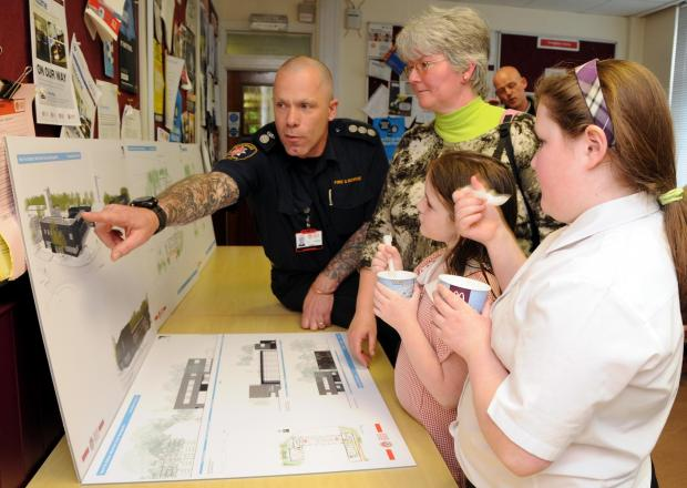 Basingstoke fire station commander Ian Wadmore shows the plans to Marie Lucas, from Hatch Warren, and her daughters Niamh and Sinéad