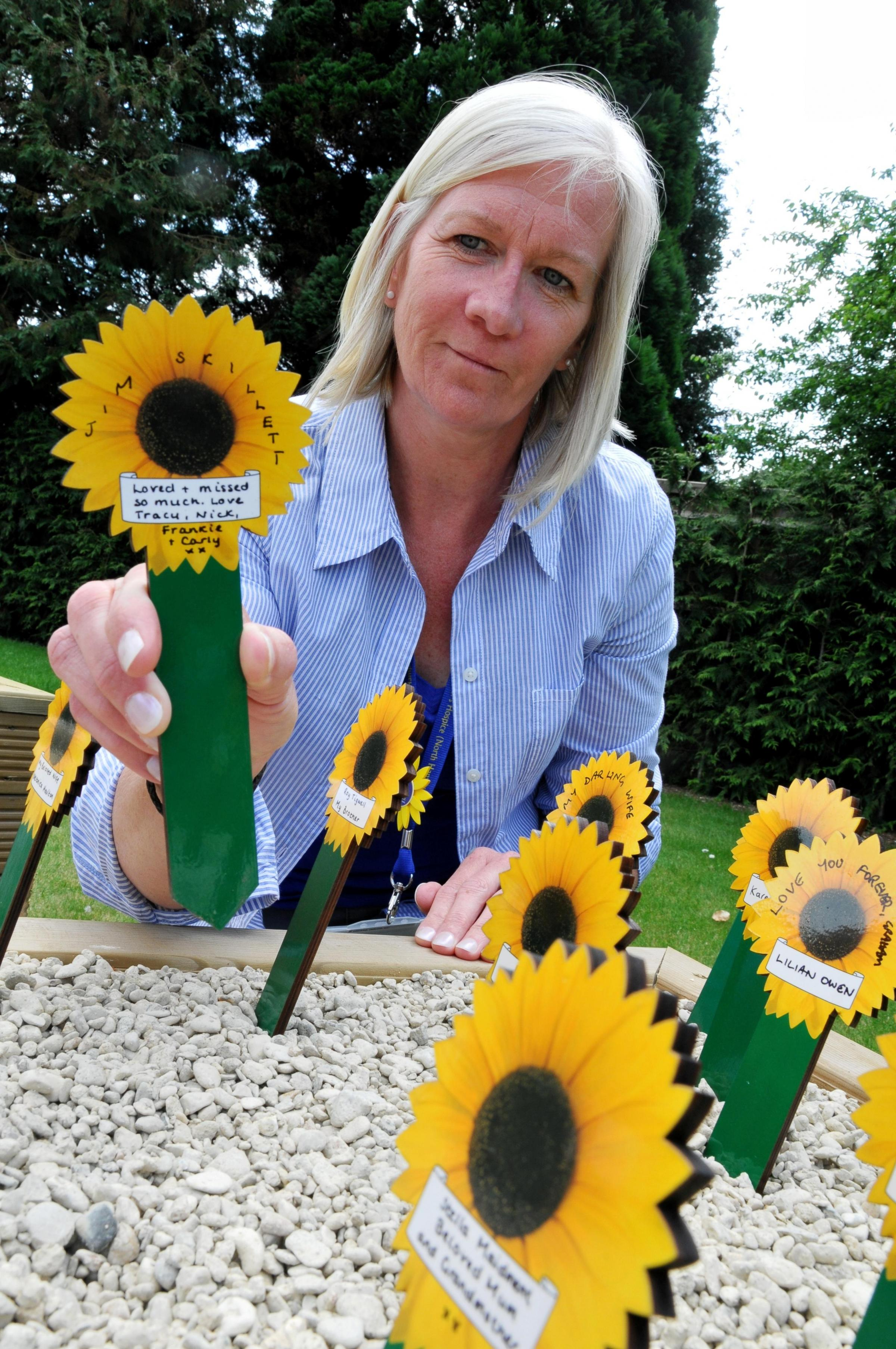 Hospice volunteer Tracey Sandle places a sunflower to remember her late husband Jim Skillett