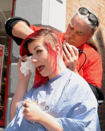 Steve Simpson shaves the head of his daughter, Alex, to raise money for the British Heart Foundation