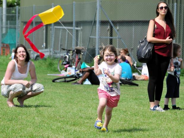 Freya Dillow, three, flies the kite she made at the workshop