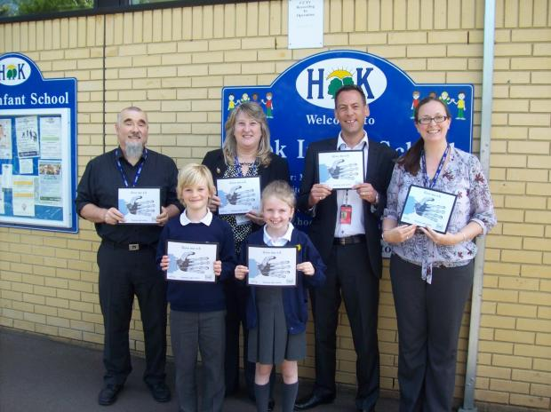 Peter West, Hook Infant School network manager, with headteacher Melanie Walker, Julian Hannan, purchasing help desk supervisor at Serco, deputy headteacher Louise Hannan, and pupils Olivia Mulholland and Edward Creed, both seven