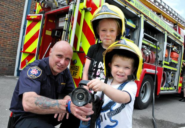 Firefighter Mark Pilbeam, from Basingstoke Red Watch, with Kaiya Cox, eight, and her brother Caison Cox