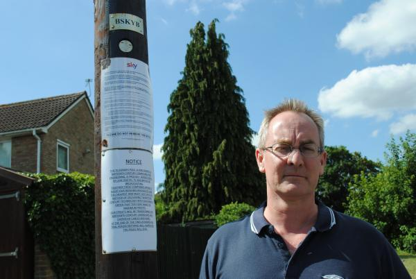Lee Douthwaite by the telegraph pole on which another resident has put a complaint notice