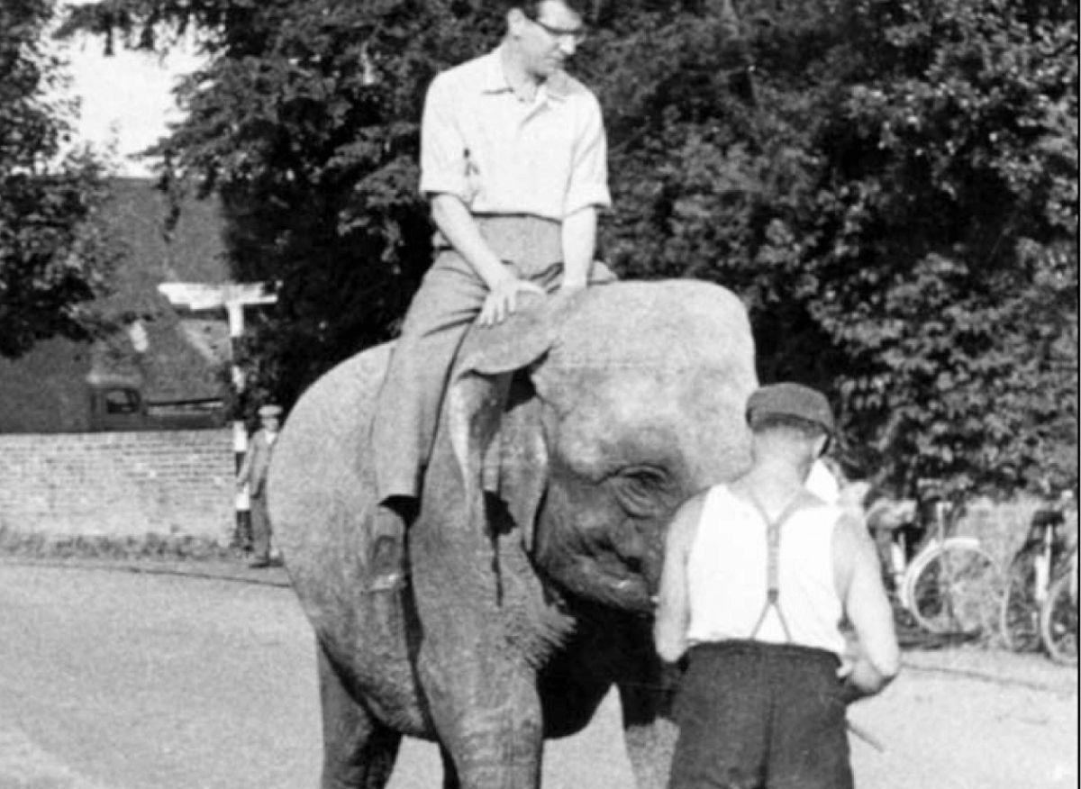 Max Bygraves enters the village on an elephant