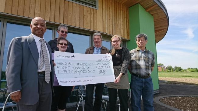 Cllr Dan Putty presents the cheque to Jeannette Welton, treasurer of the Hatch Warren and Beggarwood Community Association, second left; and Rhiannon Bullock, cafe manager, second right; watched on by cafe customers