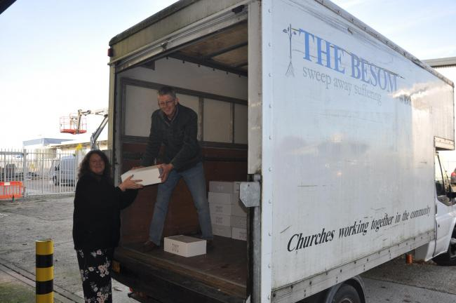 (left to right) VIVID facilities co-ordinator Angela Maskell helps volunteer Alan Jones load the Besom charity van with 200 boxes of festive treats filled by staff for Basingstoke foodbanks.