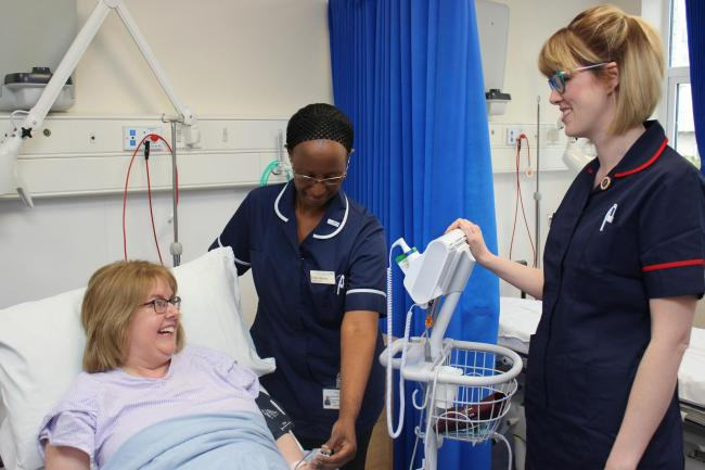 Esther Muhoza (centre), a sister on the unit, and Hayley Blandford (right), clinical matron for the unit, caring for a patient in the Emergency Surgery Ambulatory Clinic